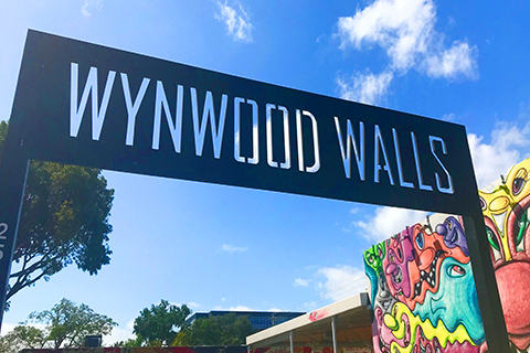 A stock photo of the sign in front of Wynwood Walls in the Wynwood Art District of Miami, Florida.